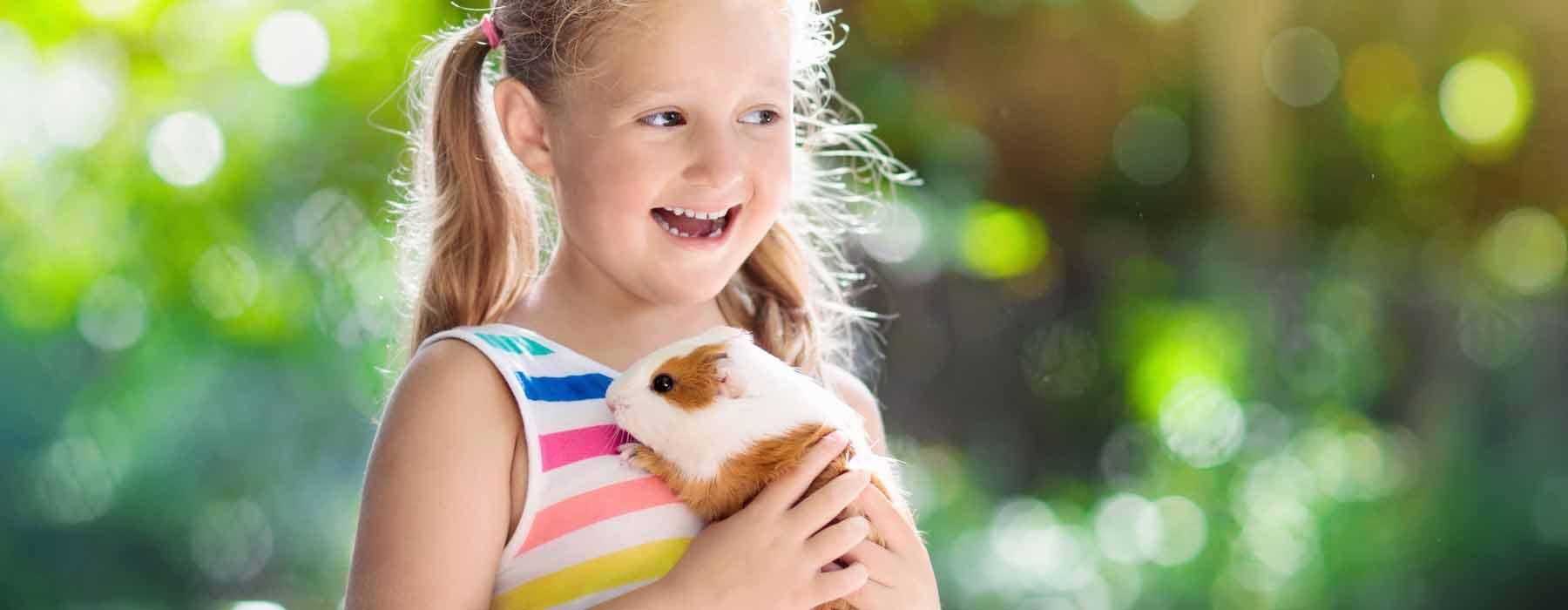 happy girl holding her guinea pig